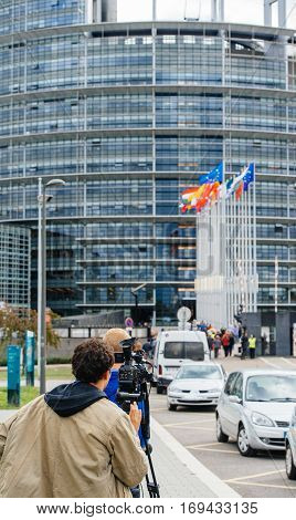 Rear view of unrecognizable journalist cameraman reporter working transmitting live in front of the European Parliament building during official Presidential visit with flags waving and people protesting