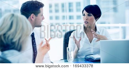 Young well dressed business people in discussion at a bright office