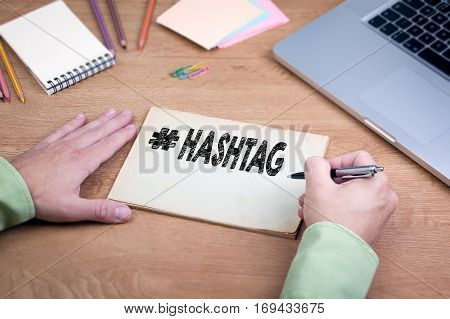 Hand writing Hashtag. Office desk with a laptop and stationery.