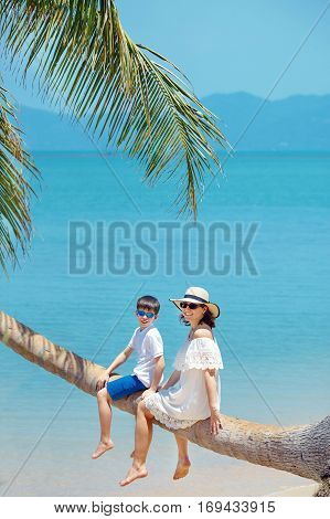 Mother and little son at tropical beach sitting on palm tree during summer vacation