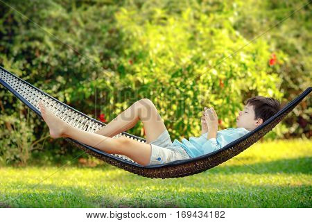Side view of cute little boy lying on a hammock looking at his cell phone and relaxing