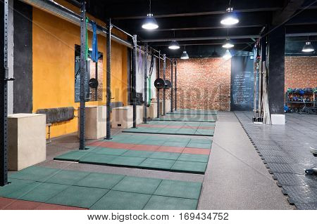 A row of horizontal bars and boxes for exercices in a cross-fit gym