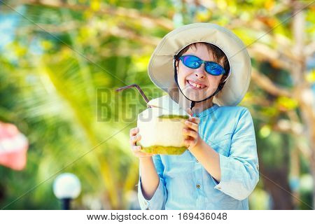 Cute little boy holding coconut cocktail on tropical beach resort