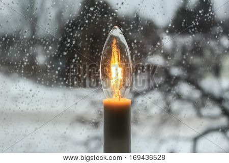 A cheery incadescent lightbulb shines at a raindrop-covered window on a rainy winter day