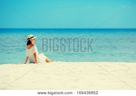 Young woman in white dress and hat lying on white sand of tropical beach having great summer time. Summer vacation, holidays, serenity, travel, lifestyle concept