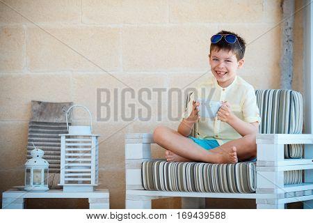 Smiling cute little boy drinking mug coffee tea hot drink on outdoor terrace