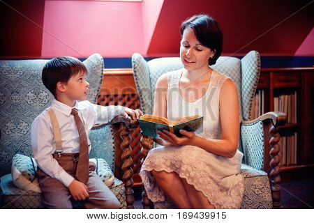Yoing mother and her little son reading a book at home