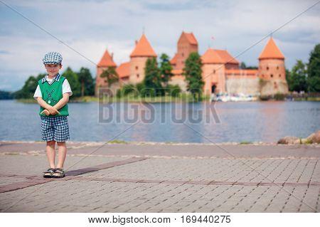 Cute little boy in front of Trakai Castle in Lithuania