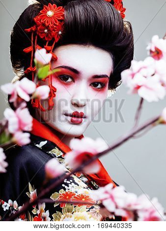 young pretty geisha in black kimono among sakura, asian oriental ethno close up