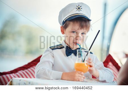 Cute toddler boy in captain costume drinking juice at indoor cafe