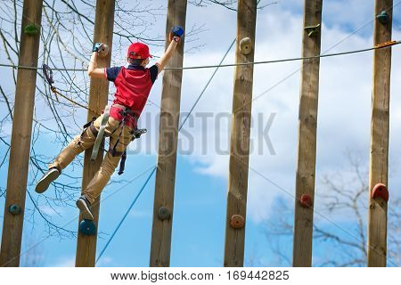 Cute little boy enjoying his time in climbing adventure park on warm and sunny summer day