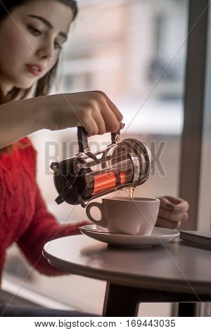 Young girl pours black tea from glass kettle to smal cup in cafe with big window