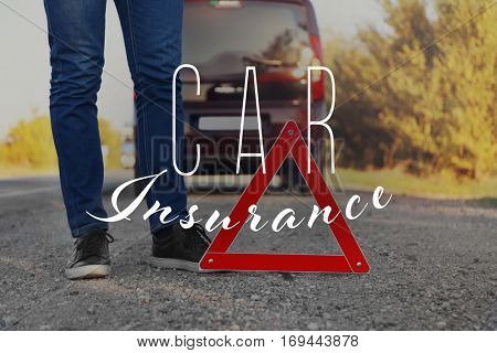 Car insurance concept. Driver standing near emergency stop sign on asphalt road