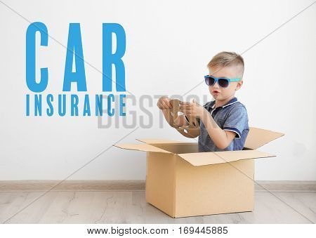 Car insurance concept. Little boy playing with cardboard box