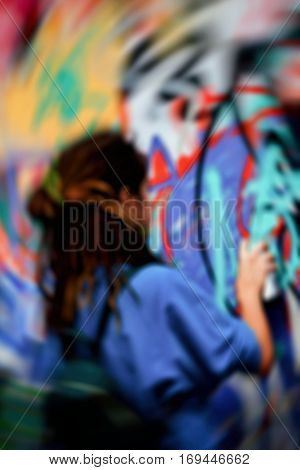 Closeup arm of young girl drawing colorful graffiti on the wall. Urban contemporary iconic culture of street youth.