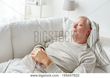old age, rest, comfort and people concept - senior man sleeping on sofa at home