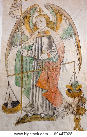 St. Michael weighing a soul devils hanging on the other side a fresco painting in Aarhus cathedral Denmark - Juni 21 2015