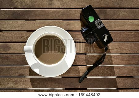 high-angle shot of a white ceramic cup with white coffee and an old camera of a rustic wooden table