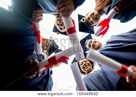 education, graduation and people concept - group of happy international students in mortar boards and bachelor gowns standing in circle with diplomas