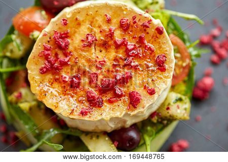 food, culinary, haute cuisine and cooking concept - close up of goat cheese salad with vegetables and dried raspberries at restaurant or cafe