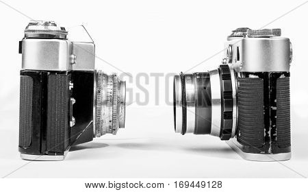 Two vintage retro camera look at each other on a white background closeup.