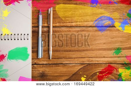 Frame of art supply against spiral notebook and pens on wooden table with copy space