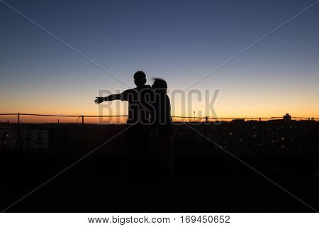 Silhouette couple playing scenario towards the sunset at roof