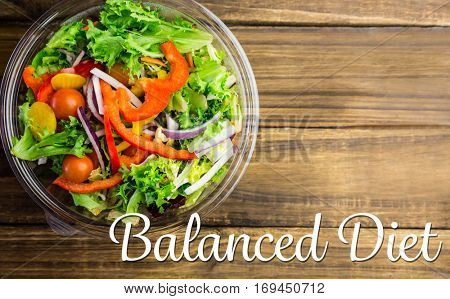 balanced diet against healthy bowl of salad on table