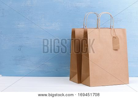 Mockup of blank shopping bags. Brown craft package. Concept for sales or discounts. Recycled paper. Blue wooden rustic board.