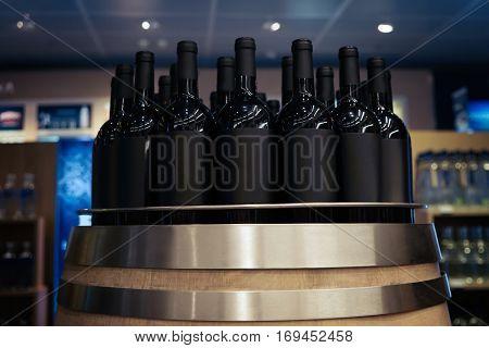 Wine bottles on wooden barrel at liquor store