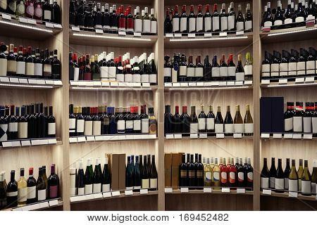 Wine bottles on wooden shelves at liquor store