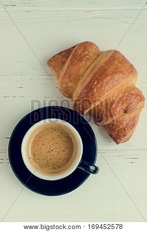 Cup of espresso coffee and fresh baked croissant on white shabby chic background. French breakfast. Top View.
