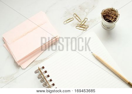 Overhead flat lay styled desk top with pink stationary, open notebook, pencil and paper clips