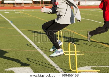 An athlete at track and field practice jumps over yellow hurdles on a green turf field