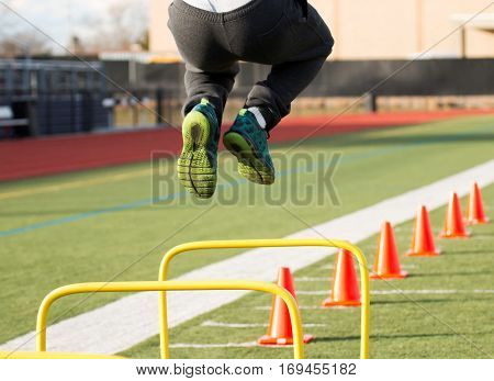 A track and field athlete jumps over yellow hurdles before he funs over orange cones all on a green turf field