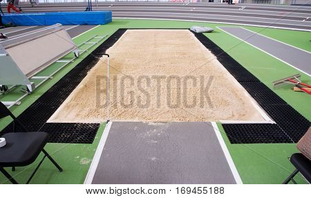 a long jump/triple jump pit is full of sand and ready for competition