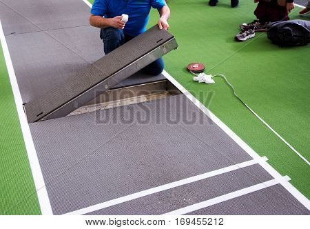A long jump board is replaced on a long jump triple jump runway in an indoor track and field arena.