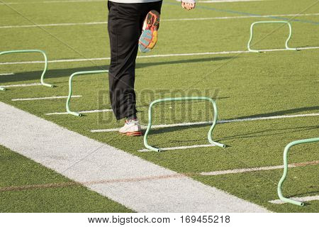 A track and field sprinter runs over green banana hurdles on a green turf field during practice