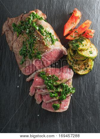 Roast Beef dinner with roasted zucchini, pepper and salsa verde on a stone plate