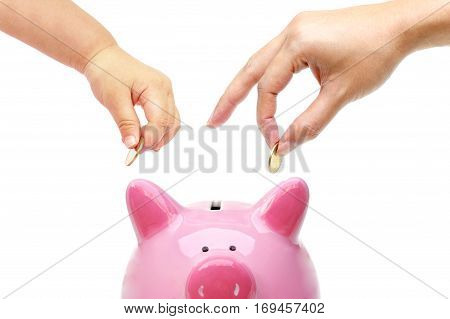 Mother and a baby do saving money in a pink piggy bank / Teaching young kid to save money