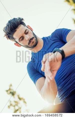 Fitness man checking performance after training.Runner training and checking stopwatch.