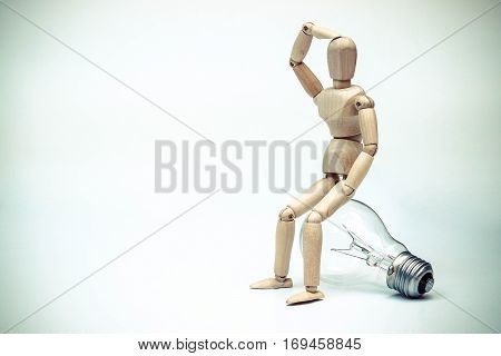 Wood Figure Mannequin sitting on an incandescent light bulb / Being stupid / Having no idea