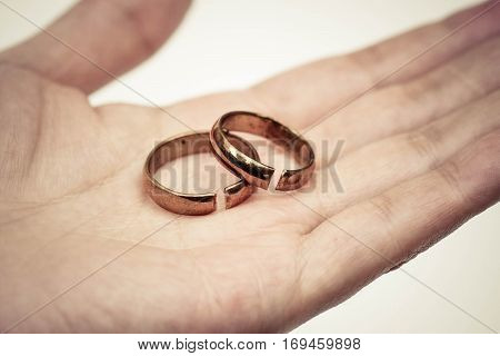 Hand holding broken rings / Divorce cond ending relationship concept