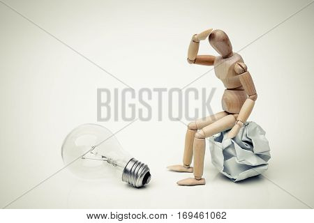 Wood figure mannequins sitting on a crumpled paper ball watching an incandescent light bulb / Business success and faliure concept