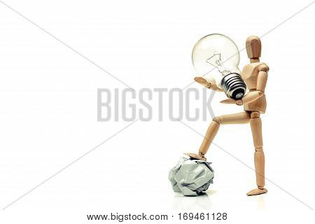 Wood figure mannequins carrying an incandescent light bulb and stepping on a crumpled paper ball / Change / Business with new idea and success concept