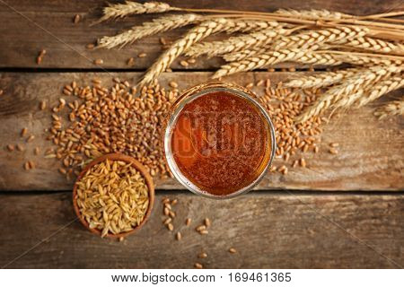 Malt in bowl and glass of beer on wooden background
