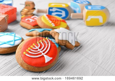 Tasty glazed cookies for Hanukkah on light wooden table, closeup