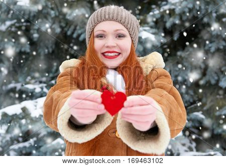 beautiful woman on winter outdoor posing with heart shape toys, holiday concept, snowy fir trees in forest, long red hair, wearing a sheepskin coat