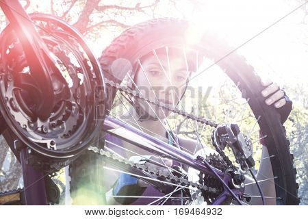 Female cyclist repairing her bicycle in park on sunny day