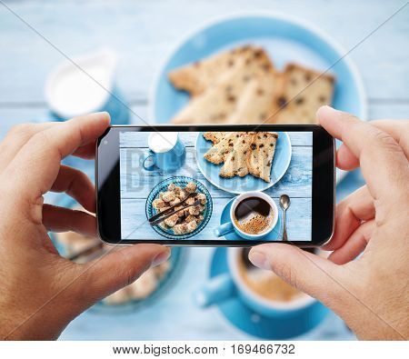Taking photo of one's breakfast with cup of coffe by smartphone.  Closeup view of  process. File contains clipping paths for smartphone and hands and  picture on it.